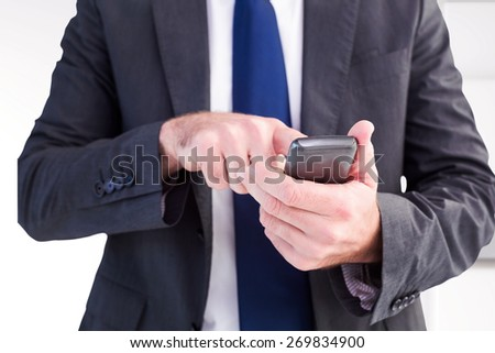 Businessman sending a text message against abstract white design