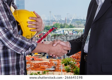 businessman shake hands with engineering in construction site - stock photo