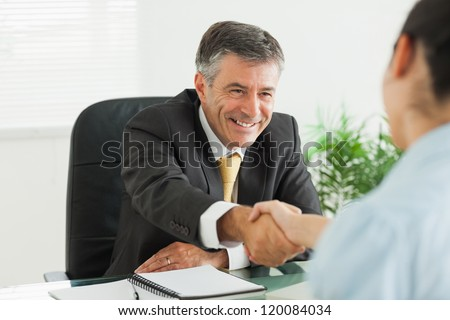 Businessman shaking a woman's hand in the office - stock photo