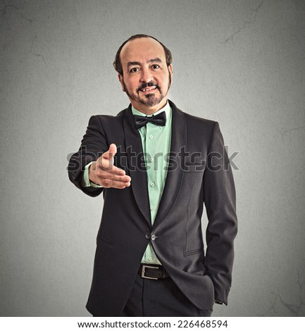 Businessman shaking hands isolated on grey office wall background. Positive face expression emotion body language  - stock photo