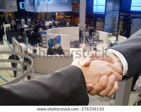 Businessman shaking hands to seal a deal with his partner. Retail event background - stock photo