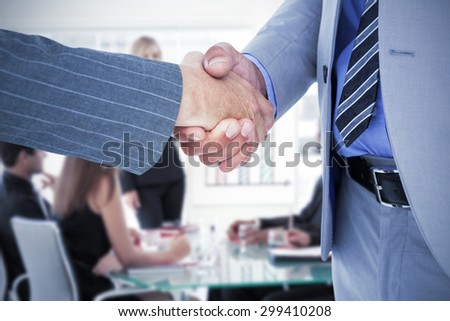 Businessman shaking hands with a co worker against businesswoman reporting to sales in a seminar - stock photo