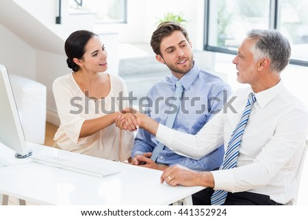 Businessman shaking hands with businesswoman in meeting at office - stock photo