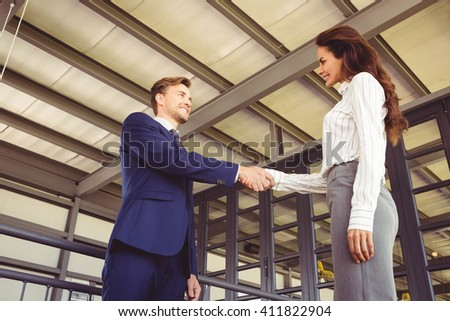 Businessman shaking hands with businesswoman in office - stock photo