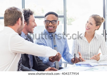 Businessman shaking hands with colleagues in meeting at office - stock photo