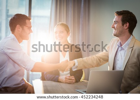 Businessman shaking hands with coworker in the office - stock photo