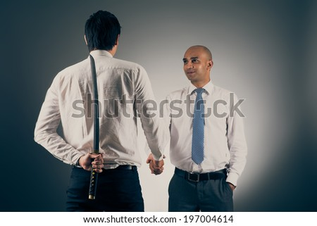 Businessman shaking hands with his partner while hiding katana sword behind his back - stock photo