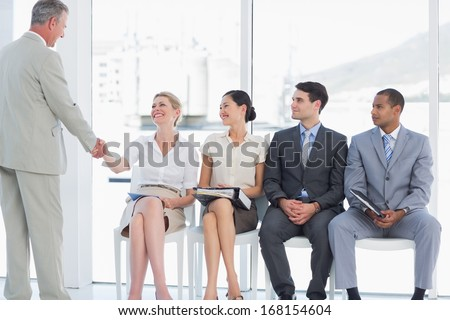 Businessman shaking hands with woman besides people waiting for job interview in a bright office - stock photo