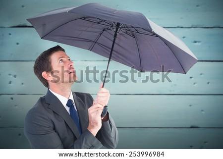 Businessman sheltering under black umbrella against painted blue wooden planks - stock photo