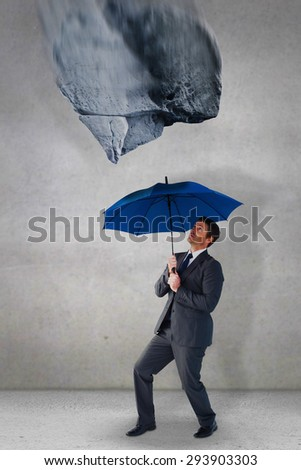 Businessman sheltering under blue umbrella against grey room