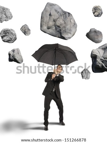 Businessman shelters from the storm of crisis - stock photo