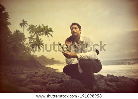 Businessman Shipwrecked on a desert island with message in a bottle. - stock photo