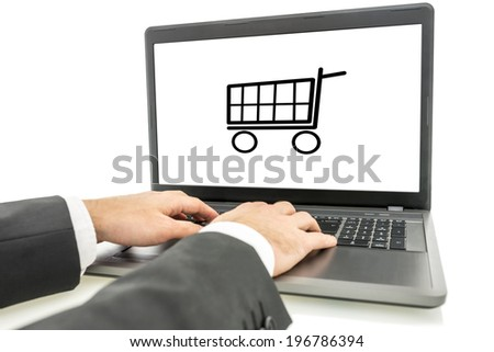 Businessman shopping online on his laptop computer with the shopping cart icon visible on his screen. - stock photo