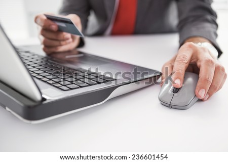 Businessman shopping online on laptop in his office
