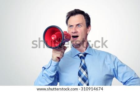 Businessman shouting into a megaphone - stock photo
