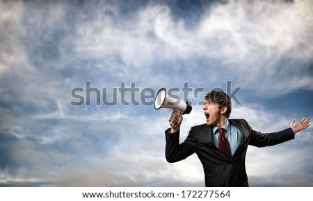 businessman shouting into a megaphone, the concept of aggression in business - stock photo