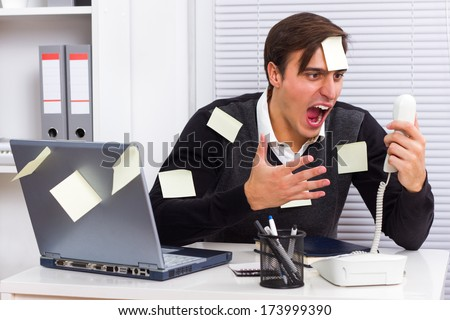 Businessman shouting on telephone at his office,Frustrated businessman - stock photo