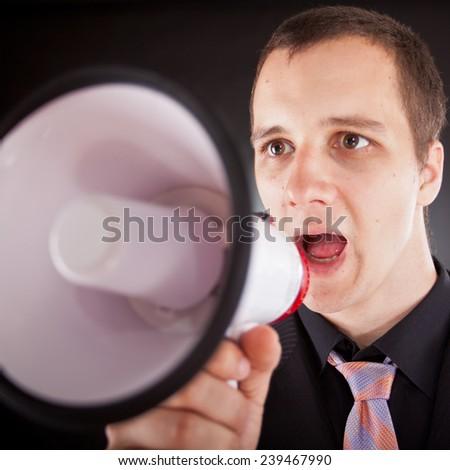 businessman shouting through megaphone in studio - stock photo