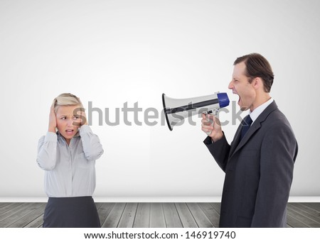 Businessman shouting with a megaphone at his scared colleague - stock photo