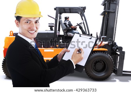 Businessman showing a clipboard while smiling at the camera with a forklift on the background