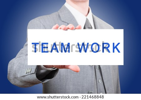 Businessman showing a large card with text Team Work - stock photo