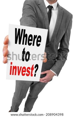 businessman showing a signboard with the text where to invest? written in it - stock photo
