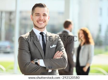 Businessman showing a smile in front on the camera with his coworkers - stock photo