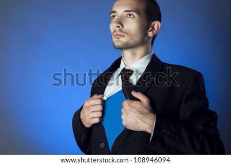 Businessman showing a superhero suit underneath his suit - stock photo
