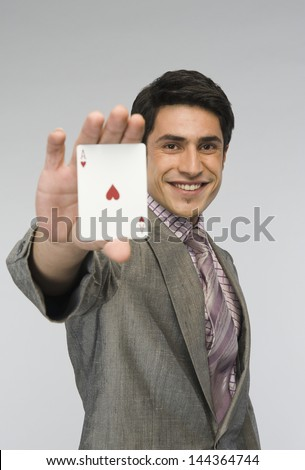 Businessman showing ace of hearts card