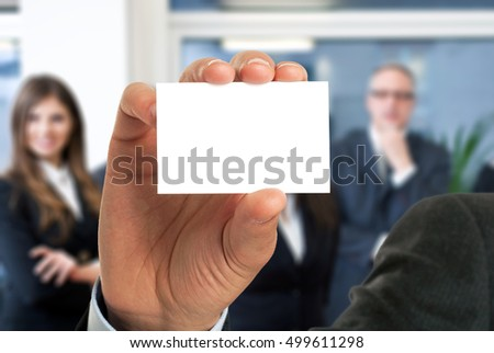 Businessman showing an empty business card in front of his colleagues