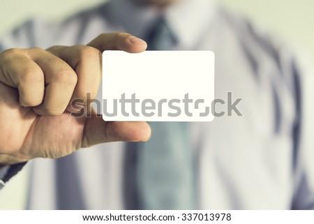 businessman showing business card ,Man's hand showing business card ,closeup shot - stock photo
