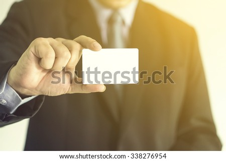 businessman showing business card ,Man's hand showing business card ,closeup shot,vintage color. - stock photo