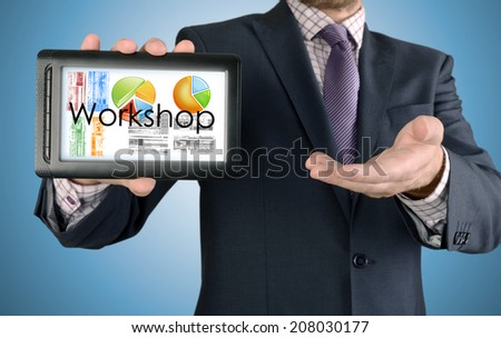 Businessman showing business concept on tablet - Workshop