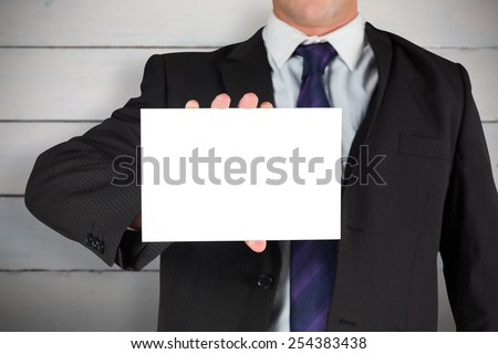 Businessman showing card against painted blue wooden planks - stock photo