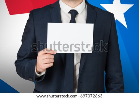 Businessman showing card to camera against digital composite of american flag
