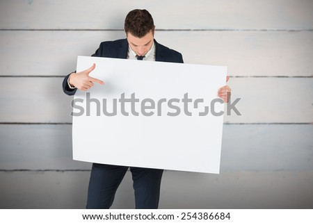 Businessman showing card to camera against painted blue wooden planks - stock photo