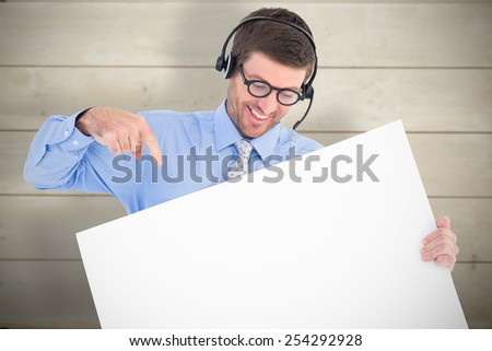 Businessman showing card wearing headset against bleached wooden planks background - stock photo