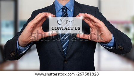 Businessman showing card with Contact Us text. Phone and mail icon. Communication concept. Isolated on office. Stock Image  - stock photo