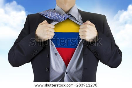 businessman showing Colombia flag underneath his shirt over blue sky - stock photo