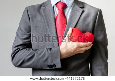 Businessman showing compassion holding red heart onto his chest in suit - crm, service mind business concept