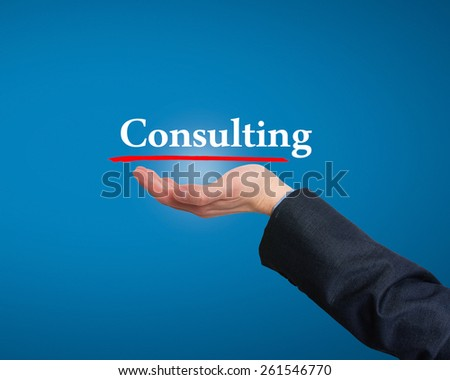 Businessman showing Consulting sign against blue. Stock Photo - stock photo