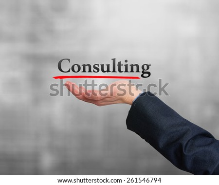 Businessman showing Consulting sign against grey. Stock Photo - stock photo