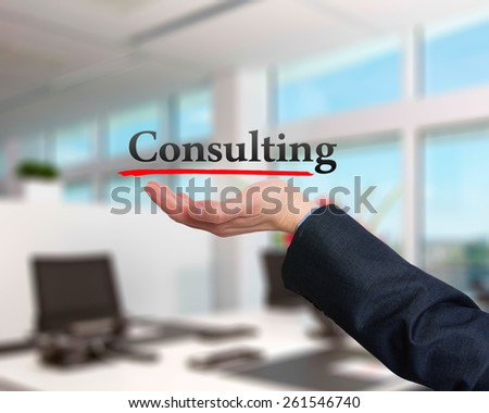 Businessman showing Consulting sign against office. Stock Photo - stock photo