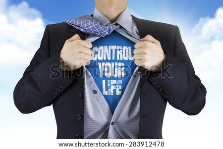 businessman showing Control your life words underneath his shirt over blue sky - stock photo