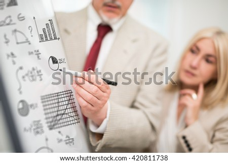 Businessman showing data on a whiteboard during a meeting - stock photo