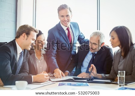 Businessman showing file to coworkers in conference room during meeting at office