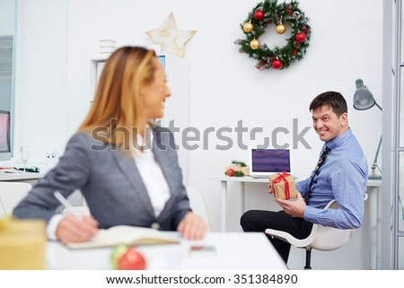 Businessman showing gift-box to colleague in office on Christmas day - stock photo
