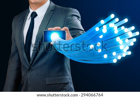 businessman showing glow fiber optic cable from smart phone - stock photo