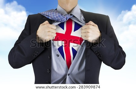 businessman showing Great Britain flag underneath his shirt over blue sky - stock photo