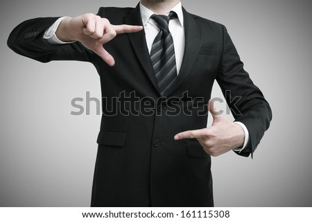 businessman showing hand square on a gray background - stock photo